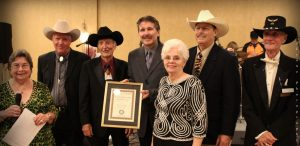 A.S.E. executive co-director Phyllis Cole (left) presents Bluegrass Band of the Year to Randall Franks (fourth from left) and the Georgia Mafia Bluegrass Band – from left, Pete Hatfield, Jerry Burke, Helen Burke, J. Max McKee, and Rick Smith. (Photo: JLynne Photography)